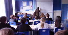4k, Group of school kids sitting and listening to teacher in classroom from back - stock footage