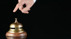 Hand ringing in service bell on wooden table on black background Stock Footage