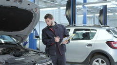 Mechanic examines car at the service Stock Footage