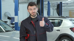Mechanic shows his thumb at the car service Stock Footage