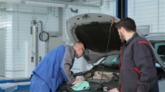 Mechanic troubleshoots car problem at the car service Stock Footage