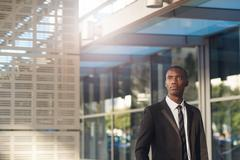 Optimistic young African businessman with office building and flare Stock Photos