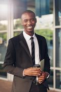 Smiling African businessman with takeaway coffee on city sidewalk Stock Photos