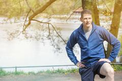 Man standing outdoors at bench and is strechting Stock Photos