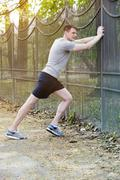 man in sportswear standing outside and strechting - stock photo