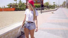 Young woman walking while holding skateboard Stock Footage