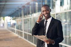 Young African businessman using his phone on a city sidewalk Stock Photos