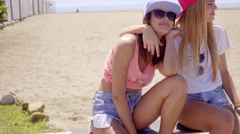 Gorgeous blond and brunette friends on stone wall - stock footage
