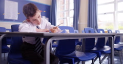 4k, Determined young school boy doing his homework in an empty class room Stock Footage