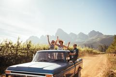 Group of young friends riding in pickup truck - stock photo
