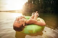 Young woman relaxing on inner tube in water Stock Photos