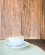 Coffee latte cup on corner of wooden background - stock photo