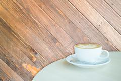 White cup of coffee latte on wooden backgound - stock photo