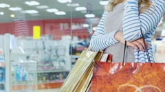 Attractive female shopper with dyal shopping bags standing at the shop window Stock Footage