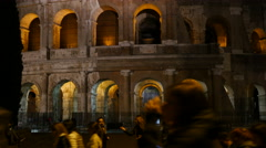 Tourists walking by Colosseum at night in Rome Italy Stock Footage