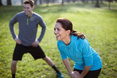Young man and woman doing warm up training in park Stock Photos