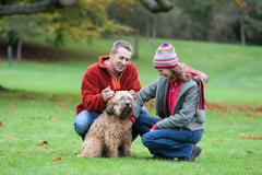 Heterosexual couple in park, crouching, stroking dog - stock photo