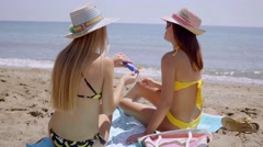 Young women applying sunscreen Stock Footage