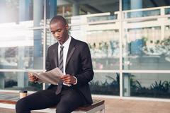 Young African entrepreneur in city reading financial newpaper Stock Photos