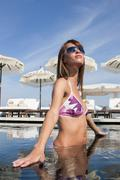 Cool young woman wearing shades standing in swimming pool at beach resort, Stock Photos