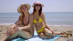 Two sexy young women sunbathing on a beach Stock Footage