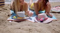 Two young women lying sun tanning on a beach Stock Footage