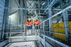 Workers on high level walkway in gas-fired power station Stock Photos