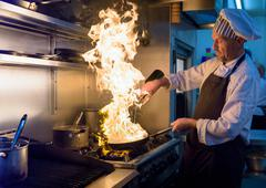 Chef with pan of flames in traditional Italian restaurant kitchen Kuvituskuvat