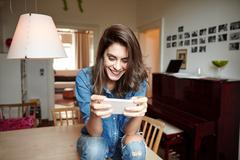 Young woman sitting on dining table reading smartphone texts - stock photo