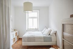 White coloured bedroom with parquet floor, bed and cupboards - stock photo