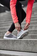 Cropped shot of mature woman training on city stairway, tying trainer laces Stock Photos