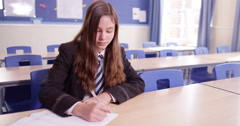 4k, Determined young school girl doing her homework in an empty class room Stock Footage