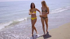 Two attractive women strolling along a beach - stock footage