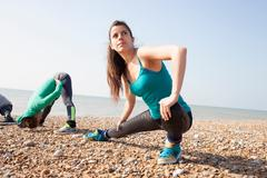 Two women doing warm up training, stretching on Brighton beach Stock Photos
