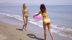 Two women in bikinis playing with a beach ball - stock footage