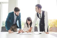 Young businesswoman and men at  boardroom table with notepad Stock Photos