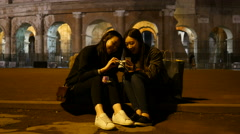 Asian Korean girls tourists have fun with photo camera by Colosseum in Rome Stock Footage
