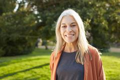 Portrait of grey haired senior woman looking at camera smiling - stock photo