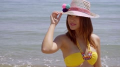 Pretty young woman in a trendy sunhat - stock footage