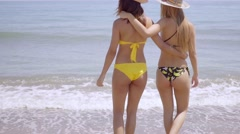 Two shapely women in bikinis walking arm in arm - stock footage