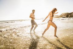 Mid adult couple wearing bikini and swimming shorts splashing in sea, Cape Town, Stock Photos