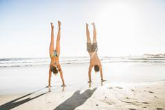 Mid adult couple doing handstands on beach, Cape Town, South Africa - stock photo
