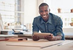 Small business owner of African descent in studio with tablet - stock photo