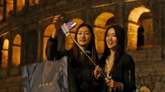 Asian Korean girl tourists take selfie by phone on stick in Rome Italy Colosseum Stock Footage