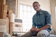 Young African business owner smiling with phone in workshop Stock Photos