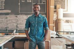 Contemporary African designer standing casually in his workshop - stock photo