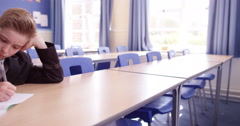 4k, A young boy doing his homework while in detention in an empty classroom Stock Footage