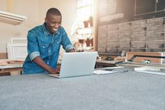 Small business owner of African descent using laptop in workshop - stock photo