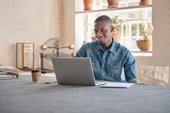 African designer working on laptop in his beautifully lit studio - stock photo