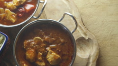 Ariel pan view of chicken and vegetable curry with rice. They are each in dif - stock footage